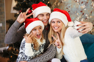 Happy young family in Santa's hat showing peace gesture while taking selfie on mobile phone