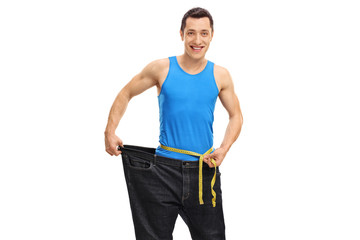 Young guy in oversized jeans measuring his waist