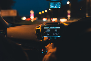 Night-time drive with the streetlights blurred out in the background and the car dashboard in focus