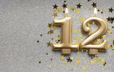 Number 12 gold celebration candle on star and glitter background