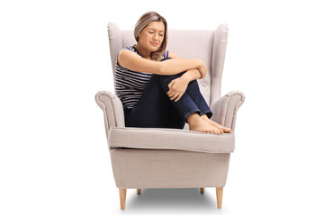 Upset young woman seated in an armchair