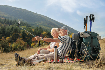 Two elderly hikers seated on a blanket taking a selfie