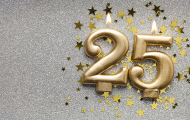 Number 25 gold celebration candle on star and glitter background