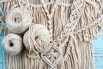 Handmade macrame braiding, background thread on a wooden Board top view