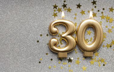 Number 30 gold celebration candle on star and glitter background