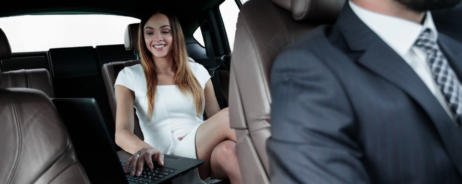 Executive businesswoman in car work on her laptop.