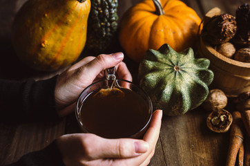 Female hands holding hot tea on rustic table with pumpkins. Autumn holiday time.