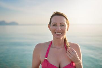 Glückliche lächelnde Frau im mittleren Alter steht am Meer