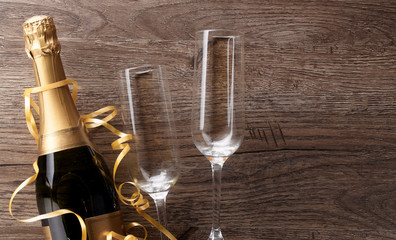 Photo of two wineglasses, bottle of champagne, gold ribbons