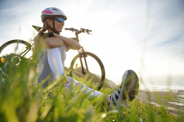 Athletic girl on bike ride, relaxing by the sea