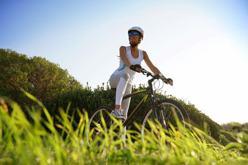 Woman in sports outfit riding bike on country track
