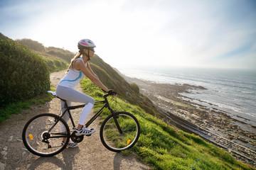Woman riding bike by the sea