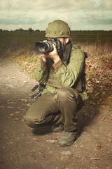Photographer in war conflict field zone shooting pictures