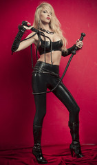 dominant blonde mistress girl in corset, gloves and bondage black leather fetish hood with ears, Bunny, posing on a red backgroung, leather whip