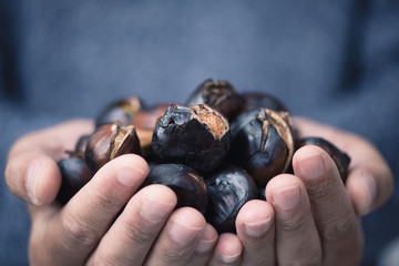 man with roasted chestnuts in his hands