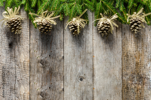 wooden background with christmas decoration golden pine cones