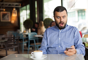 Portrait of shocked man looking at phone