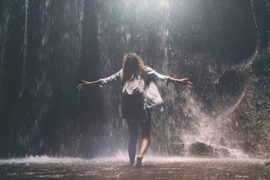 Back view photo of young woman with curly hair with hands up enjoying beautiful waterfall hidden in tropical jungles. A female is happy to see the wild waterfall in the depth of tropical forest.