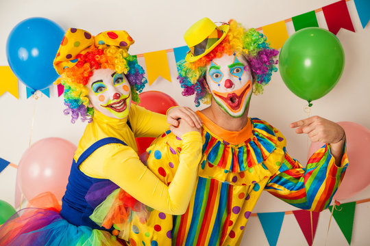 Two cheerful clowns. Birthday for children. Bright clown and clowness.