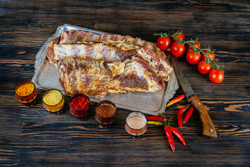 Raw uncooked Pork ribs on wooden cut board ready to cook black textured background.