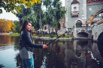 Woman taking selfie by camera near old castle