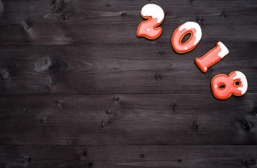 Happy new year 2018 sign symbol from red and white gingerbread cookies on dark wooden background, copy space. Top view, flat lay