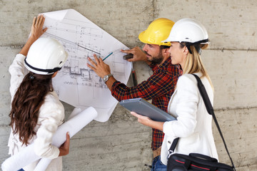 Team of inspectors and architects discuss about blueprints on construction site.