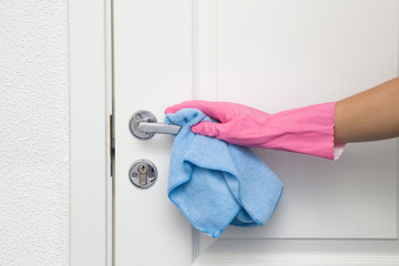 Employee's hand in rubber protective glove with rag wiping a white wooden door. Maid or housewife cares about house. Spring general or regular clean up. Commercial cleaning company concept.