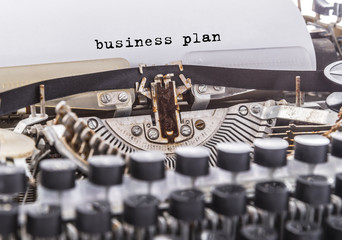 business plan is written on an old vintage typewriter. Close-up