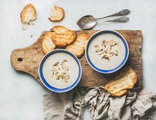 Creamy mushroom soup in bowls with toasted bread slices on rustic serving board over grey marble background, top view, selective focus