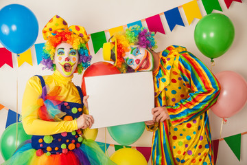 Two clowns boy and girl on holiday with white plate in hands. Birthday of the child.