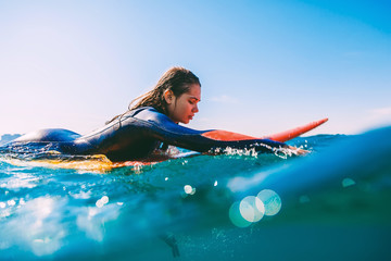 Surfer girl on surfboard. Young woman in ocean during surfing.