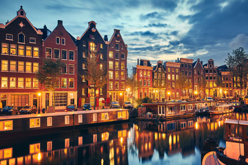 Fototapete - Evening town Amsterdam in Netherlands on bank river canal Amstel