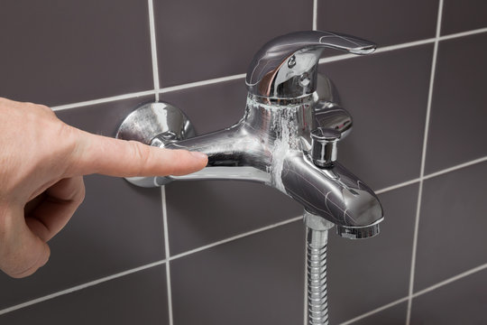 Man's hand finger pointing to calcified water tap in the bathroom. Problem concept.