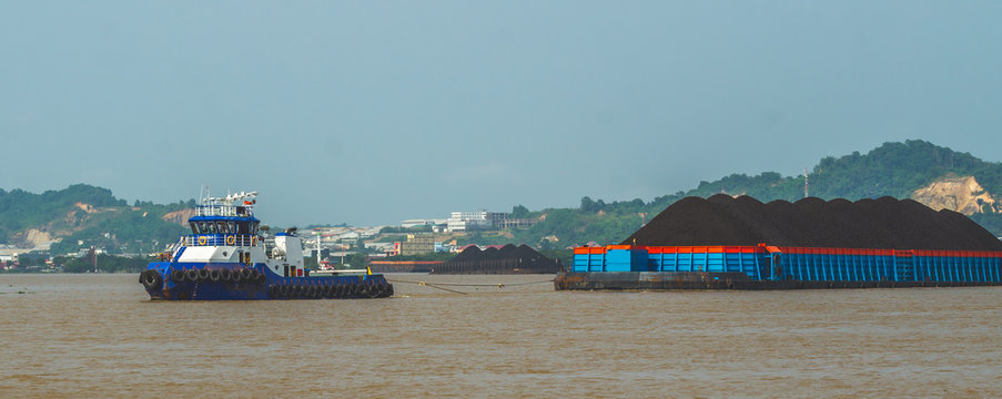 tugboat pulling heavy loaded barge of coal cruising Mahakam River in Samarinda, Indonesia