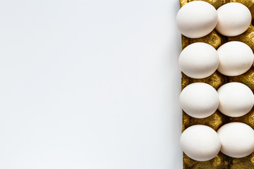 Fresh eggs on a gold support, stand in a row on a white background. There is a place for the text