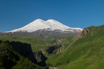 Mount Elbrus in the summer in the snow and green grass around