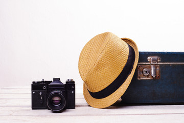 straw hat old suitcase and camera on white wooden floor near wall