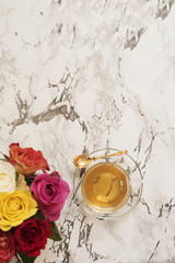 A glass cup of tea. Beautiful fresh flowers on light marble table, top view. Colorful bouquet of roses