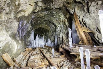 Underground mine shaft tunnel gallery witn ice frozen stalactites stalagmites