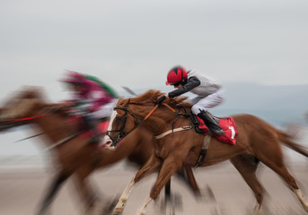Competing race horses and jockeys running on the beach, motion blur effect