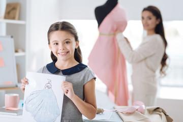 Joyful creative girl holding her drawing