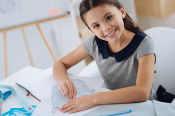 Cute positive girl making a drawing