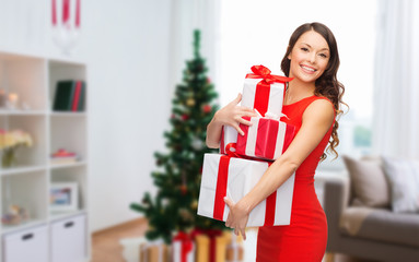 smiling woman with christmas gifts at home