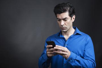 Ragazzo moro con camicia blu guarda il suo cellulare pronto a mandare un sms -  sfondo nero