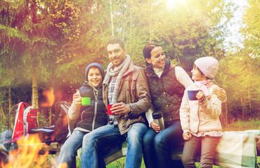 happy family drinking hot tea at camp fire