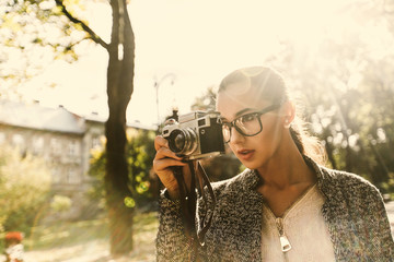Stunning young woman stands with a camera in a sunny park