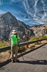Photographer in a green jacket and white hat takes a picture of the canyon and high granite mountains of Tioga Pass near Yosemite National Park. Blue sky with wispy clouds is in the background.
