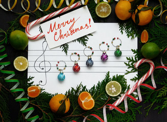 Christmas composition. Christmas decoration balls are arranged on the paper like music notes. Christmas melody concept