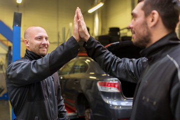 auto mechanics making high five at car shop